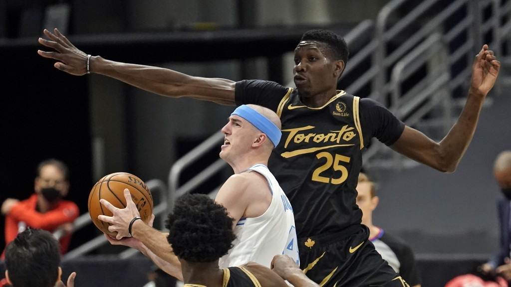 Los Angeles Lakers guard Alex Caruso (4) drive past Toronto Raptors forward Chris Boucher (25) during the second half of an NBA basketball game Tuesda...
