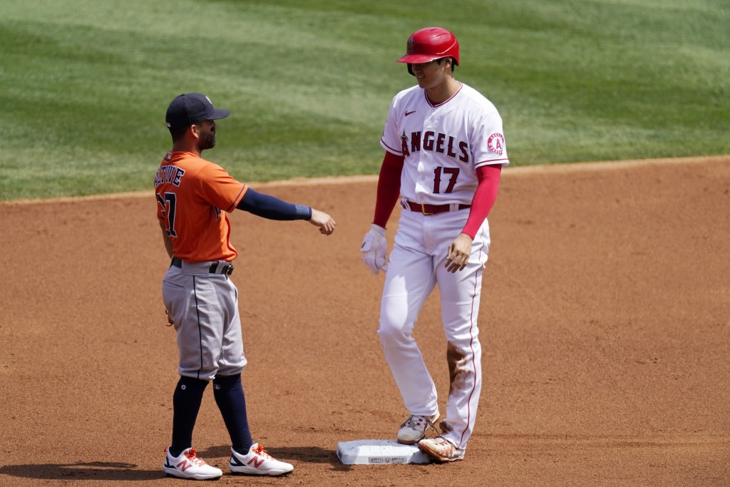 Los Angeles Angels' Shohei Ohtani, right, talks to Houston Astros second baseman Jose Altuve after stealing second during the first inning of a baseba...