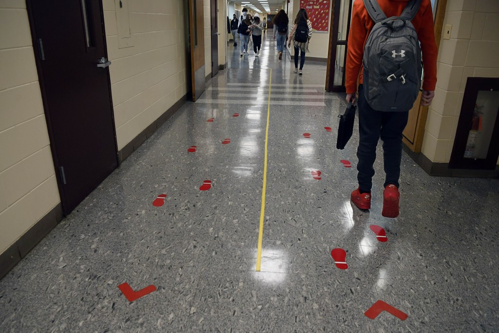 FILE - In this March 18, 2021, file photo, students stay distanced and in separate lanes when passing between classes at Windsor Locks High School in ...
