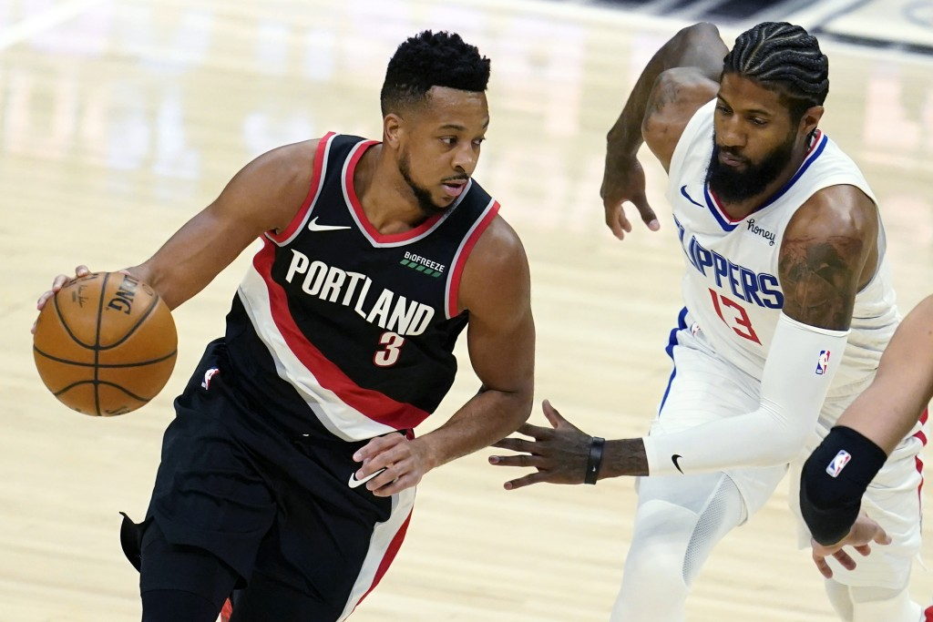 Portland Trail Blazers guard CJ McCollum (3) dribbles past Los Angeles Clippers guard Paul George (13) during the first half of an NBA basketball game...
