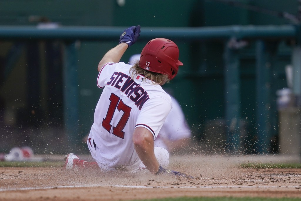 Washington Nationals' Andrew Stevenson slides across home plate for a run on Jonathan Lucroy's double in the second inning of an opening day baseball ...