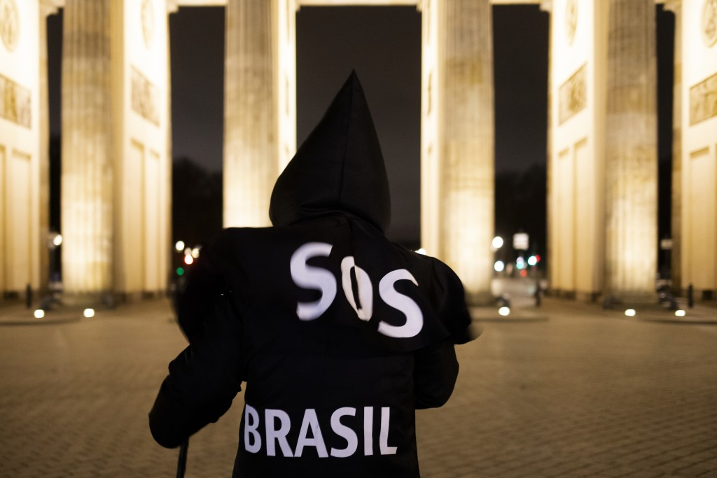 Brazilian activist and artist Rafael Puetter, dressed as the grim reaper, walks in front of the Brandenburg Gate in a one-man protest through Berlin, ...