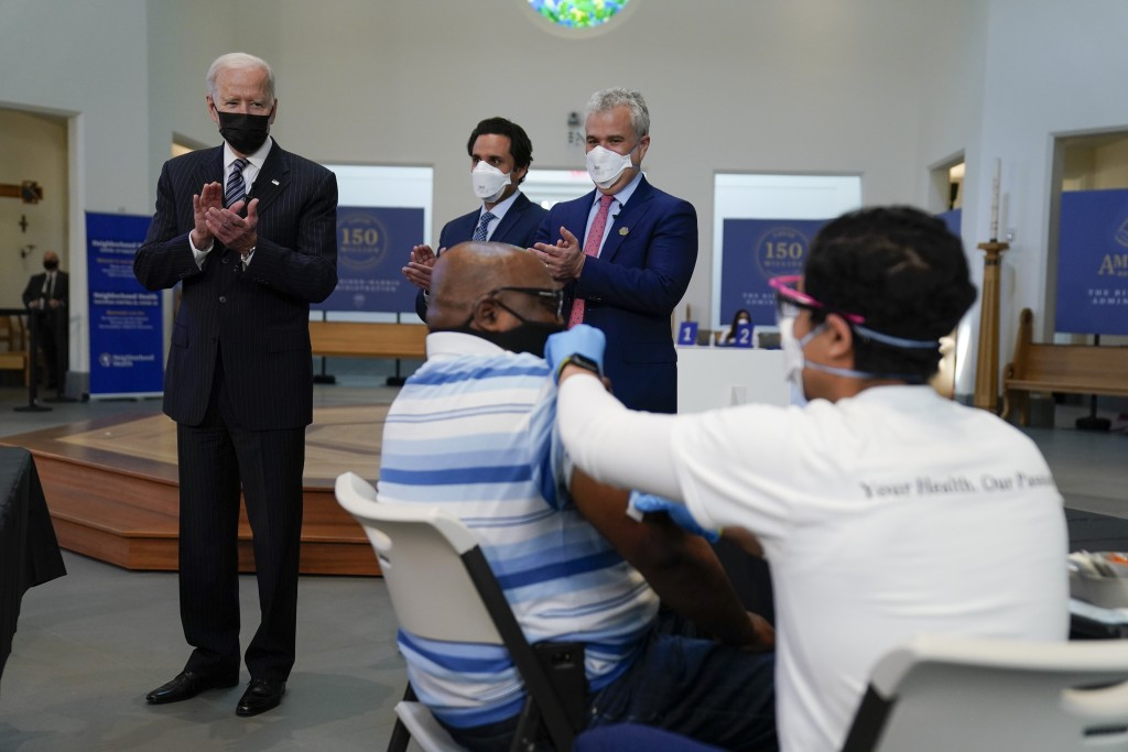 President Joe Biden applauds as a person receives a COVID-19 vaccination shot as he visits a vaccination site at Virginia Theological Seminary, Tuesda...