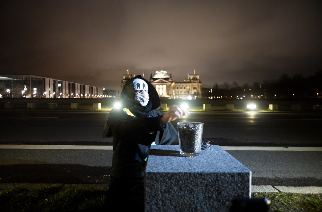 Brazilian activist and artist Rafael Puetter, dressed as the grim reaper, sits in front of the Reichstag building and counts sunflower seeds during a ...