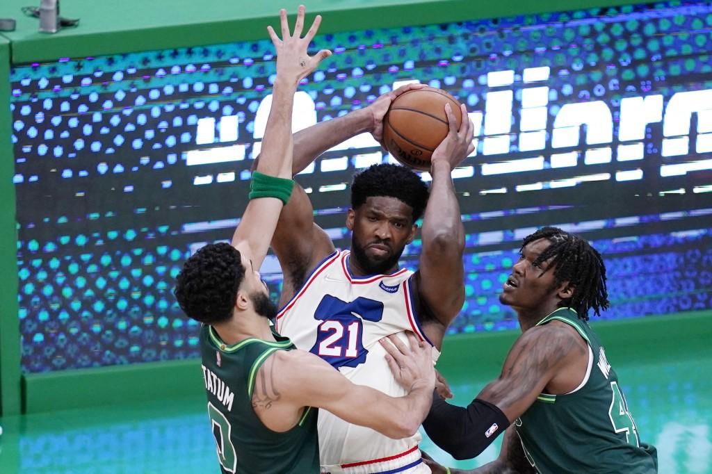 Philadelphia 76ers center Joel Embiid, center, looks to pass while pressured by Boston Celtics forward Jayson Tatum, left, and center Robert Williams ...