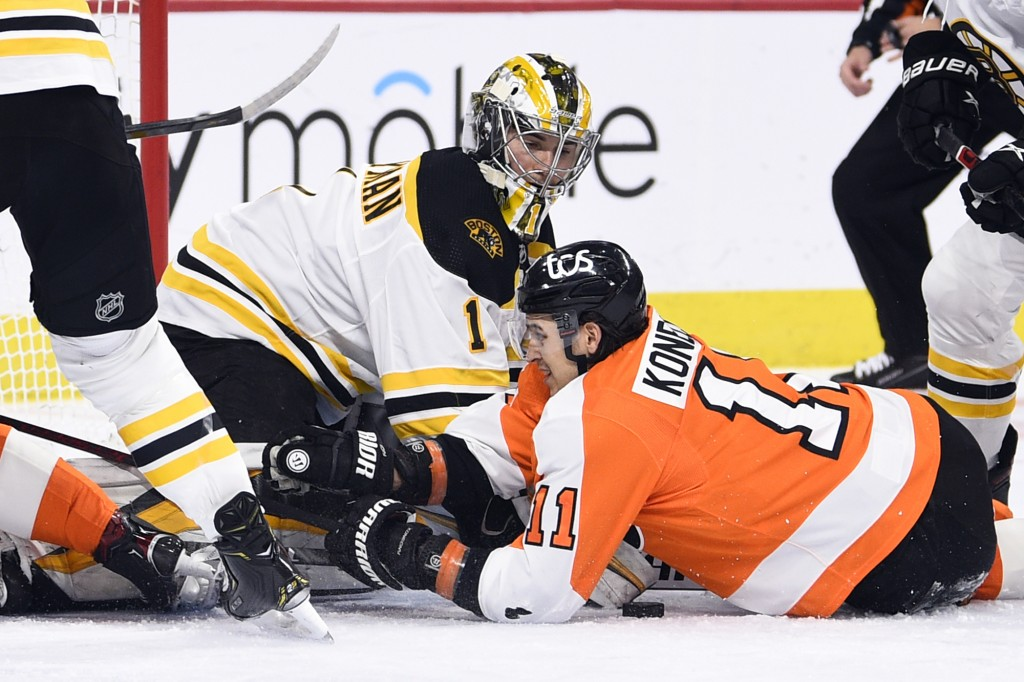 Boston Bruins goaltender Jeremy Swayman, left, makes a save as Philadelphia Flyers' Travis Konecny (11) looks for the rebound during the first period ...