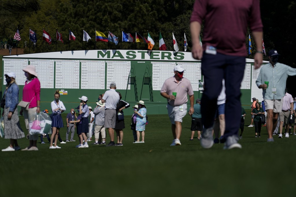 Patrons walk by the main scoreboard during a practice day for the Masters golf tournament on Tuesday, April 6, 2021, in Augusta, Ga. (AP Photo/Gregory...