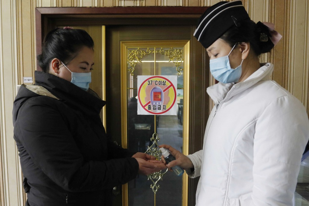 FILE - In this Feb. 5, 2021, file photo, a staff member, right, of the Pongnam Noodle House disinfects the hands of a woman coming into its restaurant...