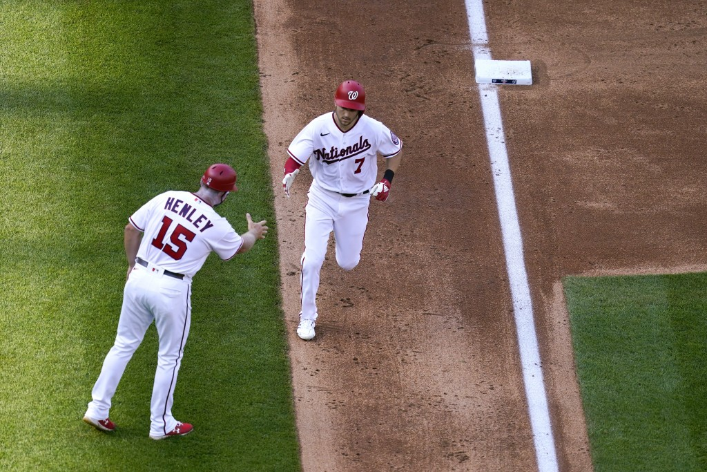 Washington Nationals' Trea Turner (7) rounds the bases past third base coach Bob Henley after hitting a two-run home run in the third inning of an ope...