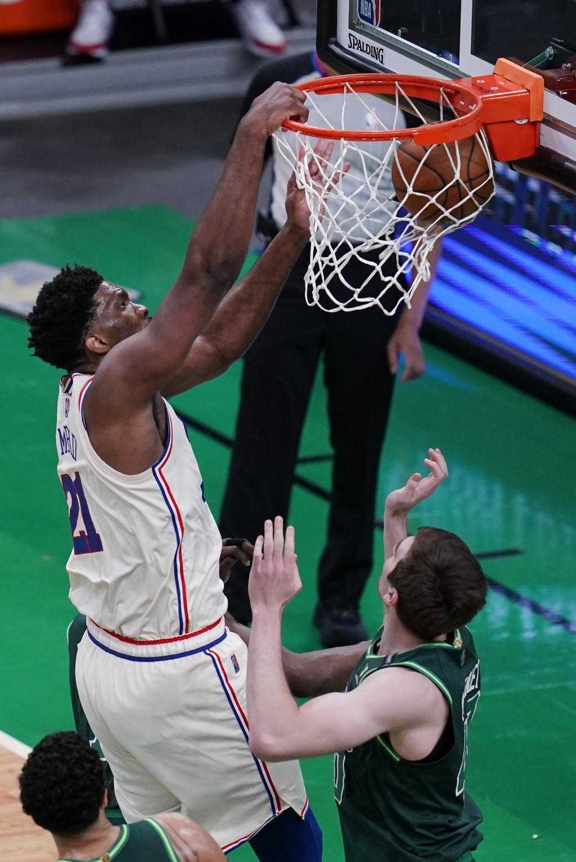 Philadelphia 76ers center Joel Embiid, left, dunks over Boston Celtics center Luke Kornet, right, during the first half of an NBA basketball game, Tue...