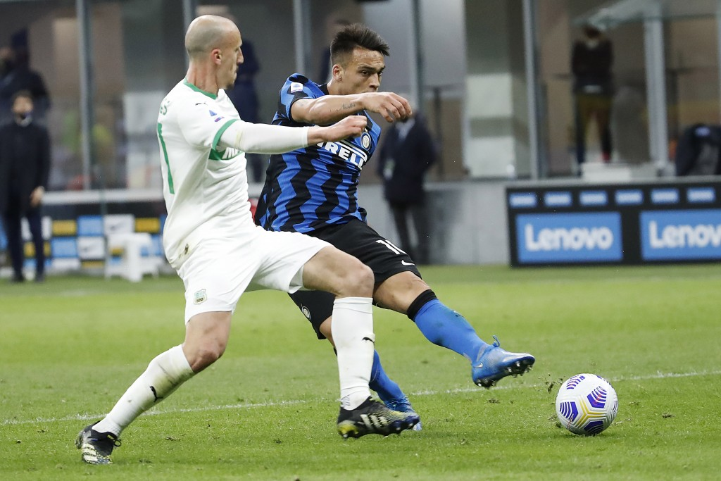 Inter Milan's Lautaro Martinez, right, scores against Sassuolo during the Serie A soccer match between Inter Milan and Sassuolo at the San Siro Stadiu...
