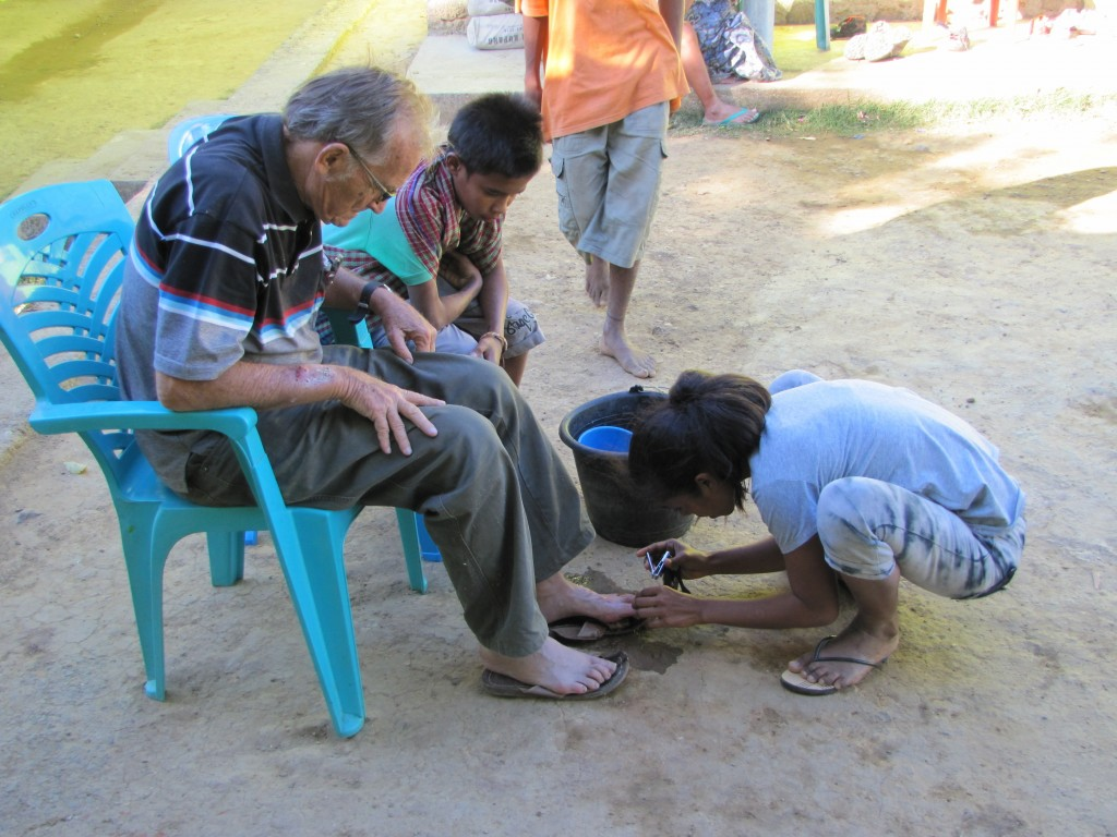 In this 2017 photo provided to The Associated Press, a young girl clips the toenails of now-defrocked Catholic priest Richard Daschbach at the Topu Ho...