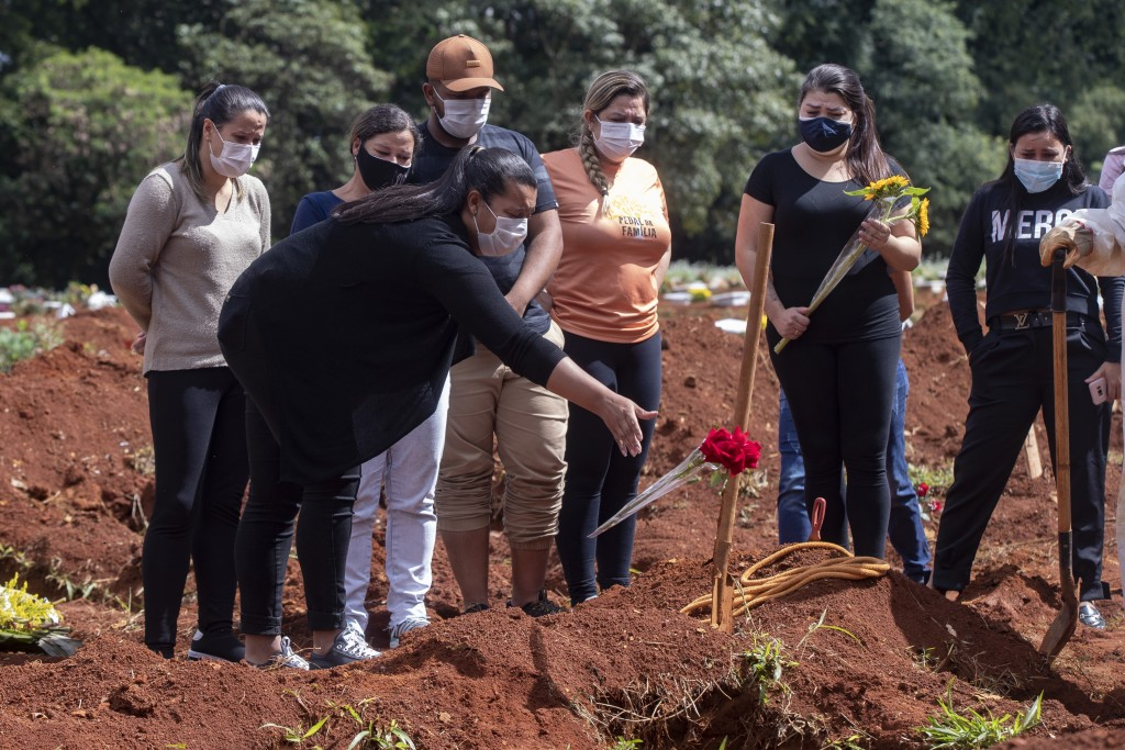 A woman throws a flower over the tomb of a relative who died from complications related to COVID-19 at the Vila Formosa cemetery in Sao Paulo, Brazil,...