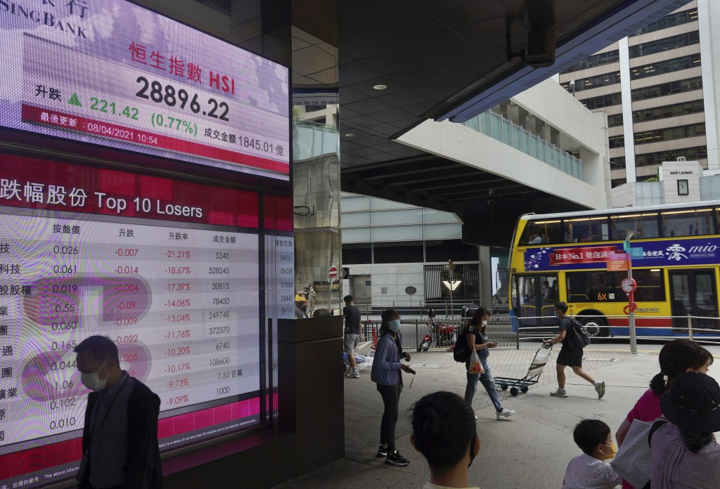 People walk past a bank's electronic board showing the Hong Kong share index in Hong Kong Thursday, April 8, 2021. Shares were mostly higher in Asia o...