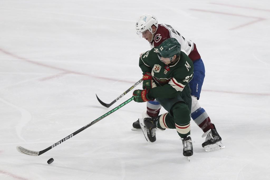 Minnesota Wild's Kevin Fiala (22) and Colorado Avalanche's Jacob MacDonald (34) go after the puck during the third period of an NHL hockey game Wednes...