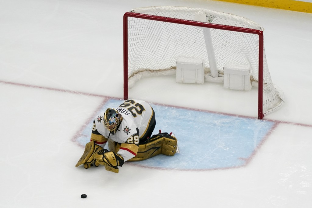 Vegas Golden Knights goaltender Marc-Andre Fleury stops a puck with his gloves after losing his stick during the third period of an NHL hockey game ag...