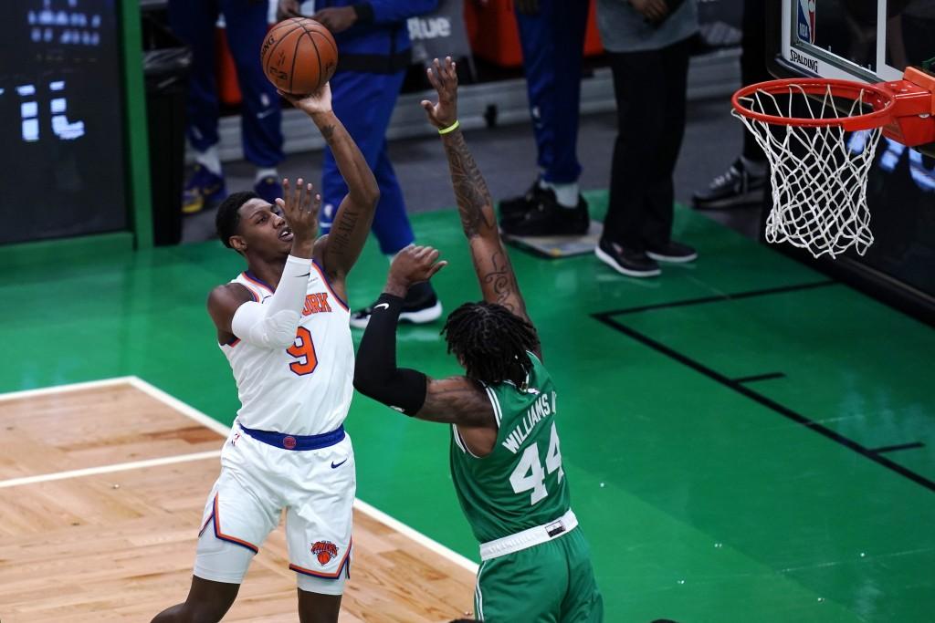 New York Knicks guard RJ Barrett (9) shoots over Boston Celtics center Robert Williams III (44) during the first half of an NBA basketball game Wednes...