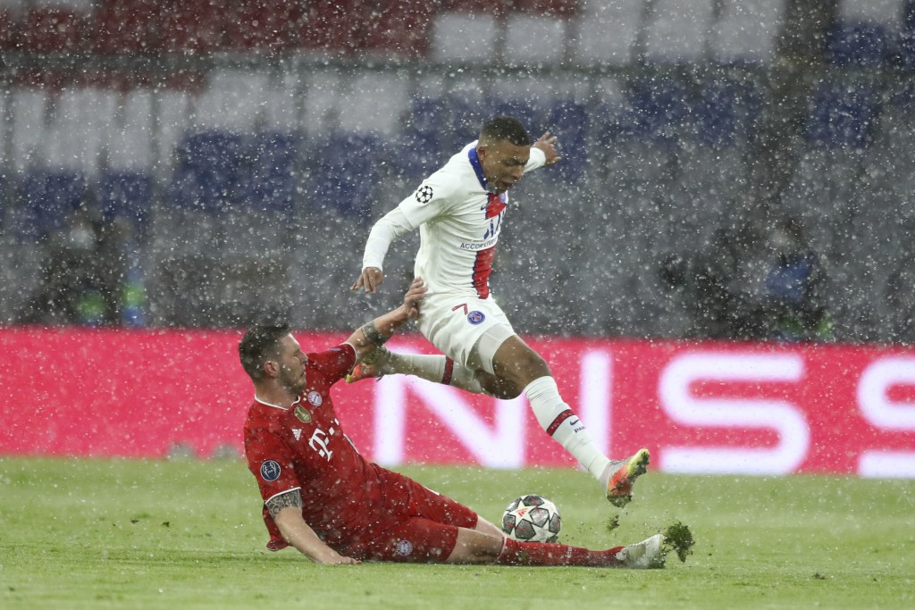 Bayern's Niklas Suele, left, tries to stop PSG's Kylian Mbappe during the Champions League quarterfinal soccer match between Bayern Munich and Paris S...