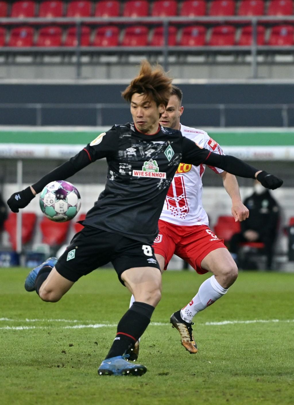 Bremen's Yuya Osako, front, and Regensburg's Benedikt Saller in action during the German soccer cup quarter final soccer match between Jahn Regensburg...