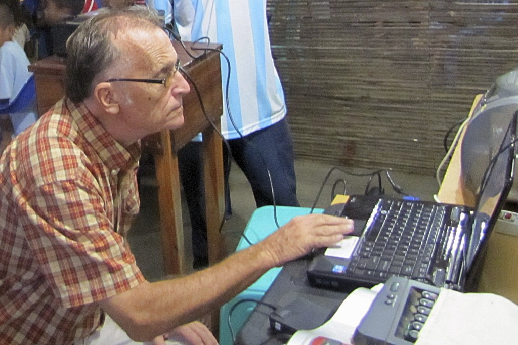 This 2010 photo provided to The Associated Press shows now-defrocked Catholic priest Richard Daschbach using a computer at the Topu Honis children's s...