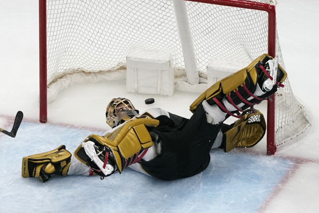 Vegas Golden Knights goaltender Marc-Andre Fleury slips as a puck flies by during the third period of an NHL hockey game against the St. Louis Blues W...