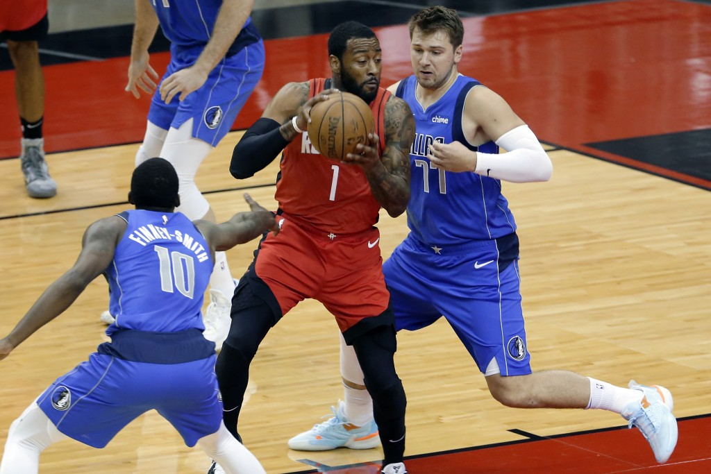 Houston Rockets guard John Wall (1) drives between Dallas Mavericks forward Dorian Finney-Smith (10) and guard Luka Doncic (77) during the first half ...