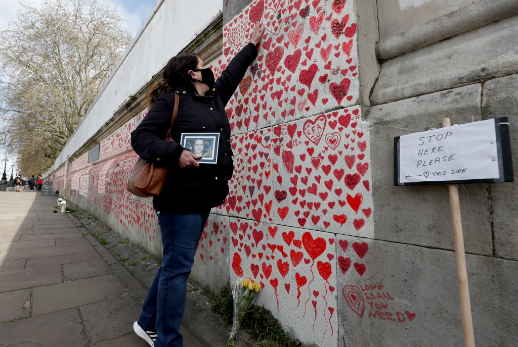 Familiy members bereaved by Covid-19 mark the completion of the approximately 150,000 hearts being painted onto the National Covid Memorial Wall, on t...