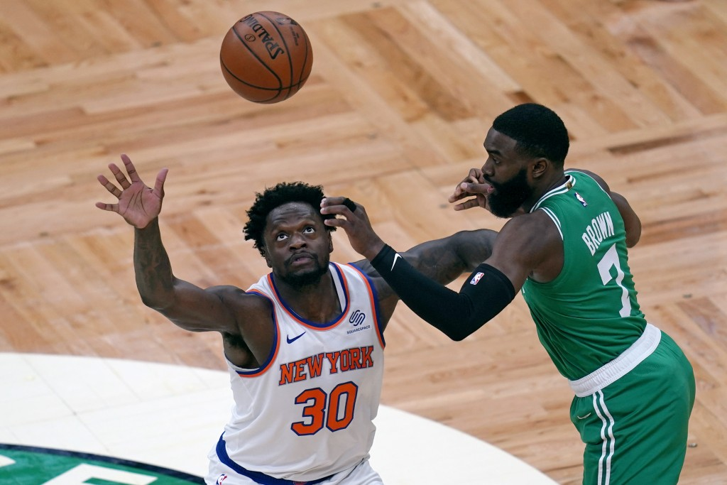 New York Knicks forward Julius Randle (30) looks up to catch a pass as Boston Celtics guard Jaylen Brown (7) defends during the first half of an NBA b...