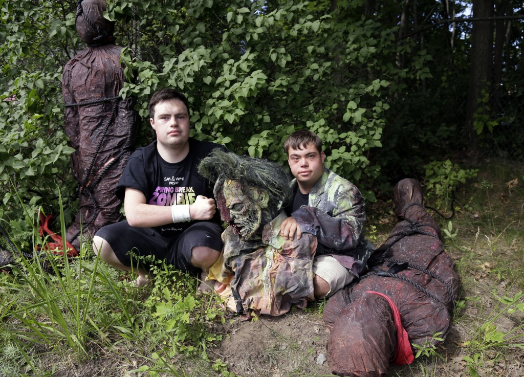 FILE - In this July 12, 2016, file photo, Sam Suchmann, left, and Mattie Zufelt pose with ghoulish figures at Sam's home in Providence, R.I. The two y...