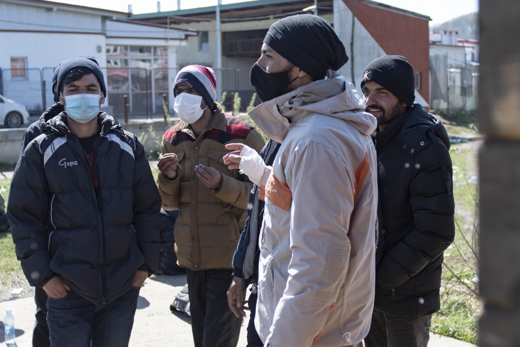 Migrants, some wearing masks for protection aganst the COVID-19 infection, speak outside the Miral camp, in Velika Kladusa, Bosnia, Wednesday, April 7...
