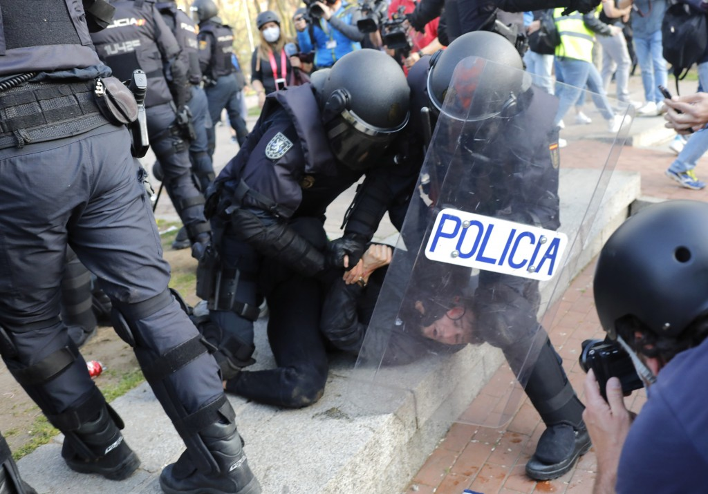 A protester is detained by Spanish police as they try to keep them away from supporters of the far-right Vox party during a party rally in Madrid's Va...
