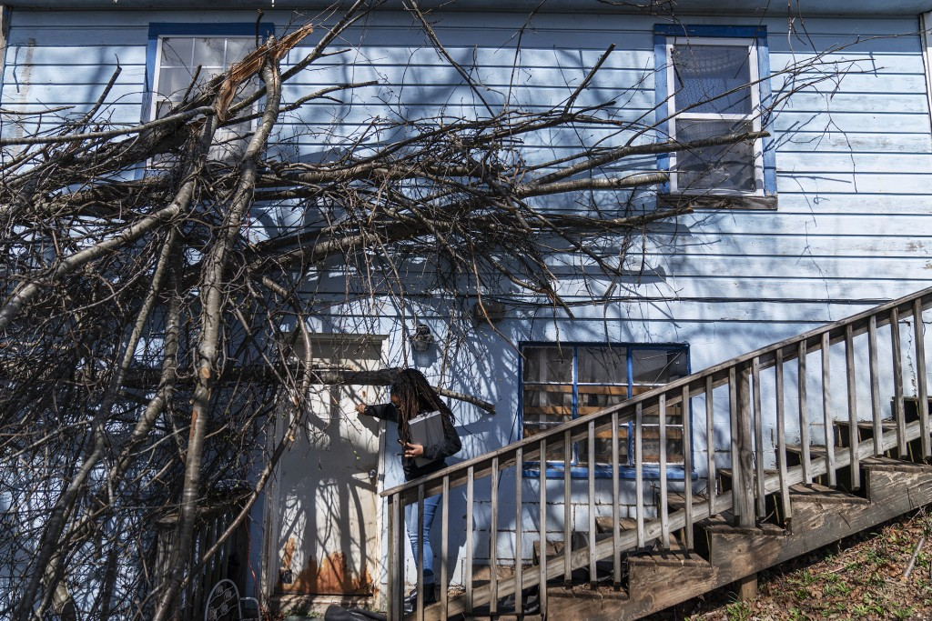 Larrecsa Cox, who leads the Quick Response Team which visits everyone who overdoses to offer help, knocks on the door of a home that suffered tree dam...