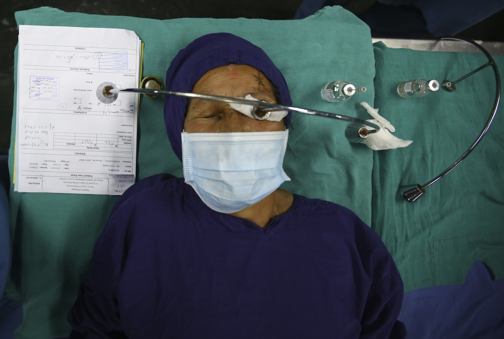 A patient lies on a hospital bed after receiving anesthesia before cataract surgery at the Tilganga Eye Center in Kathmandu, Nepal, March 26, 2021. Ne...