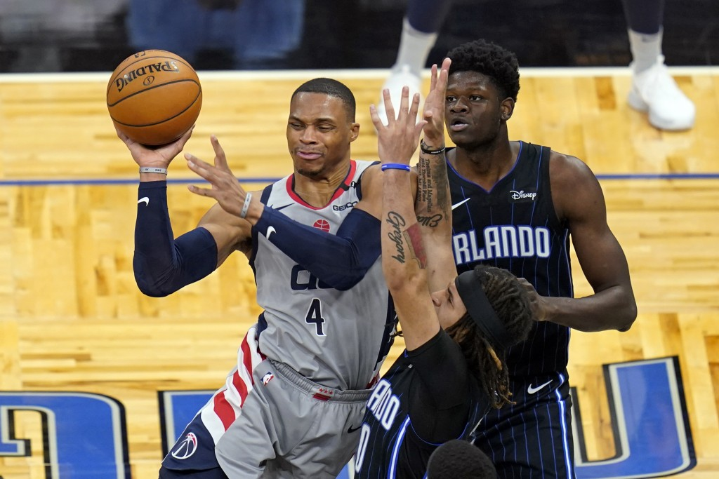 Washington Wizards guard Russell Westbrook (4) passes the ball as his path to the basket is blocked by Orlando Magic guard Cole Anthony, center, and c...