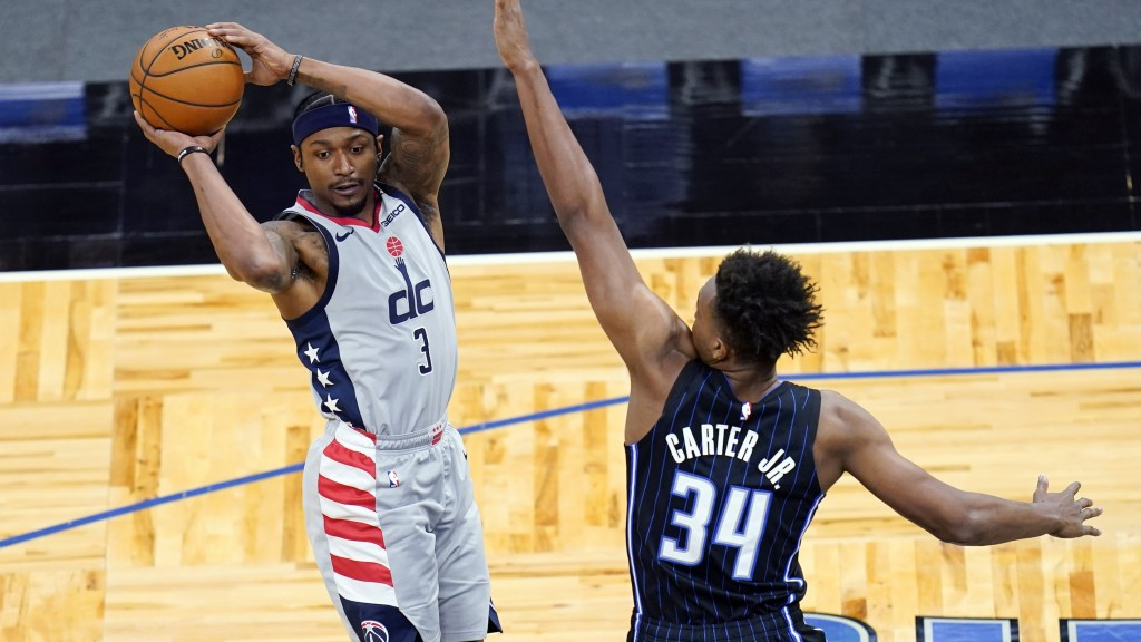 Washington Wizards guard Bradley Beal (3) passes the ball as he is defended by Orlando Magic center Wendell Carter Jr. (34) during the first half of a...