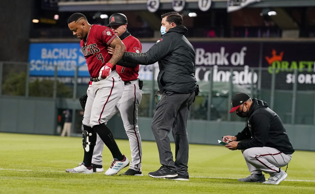 Arizona Diamondbacks' Ketel Marte, left, is helped off the field after injuring his leg while running out a ground ball during the sixth inning of the...