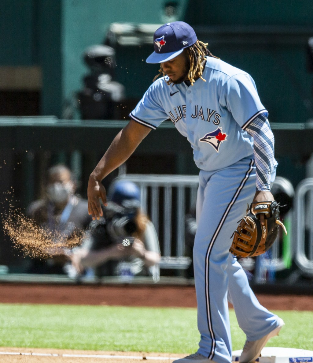 Toronto Blue Jays first baseman Vladimir Guerrero Jr. throws a fist full of dirt after failing to force out Texas Rangers' Jose Trevino during the sec...