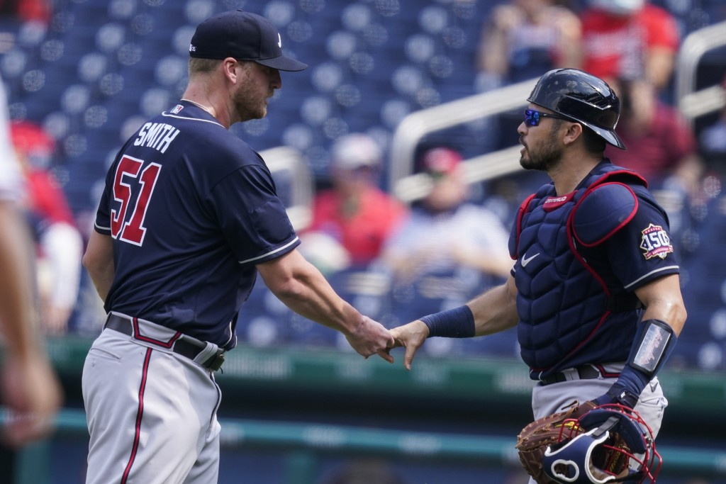 Atlanta Braves relief pitcher Will Smith and catcher Travis d'Arnaud celebrate after the first baseball game of a doubleheader against the Washington ...