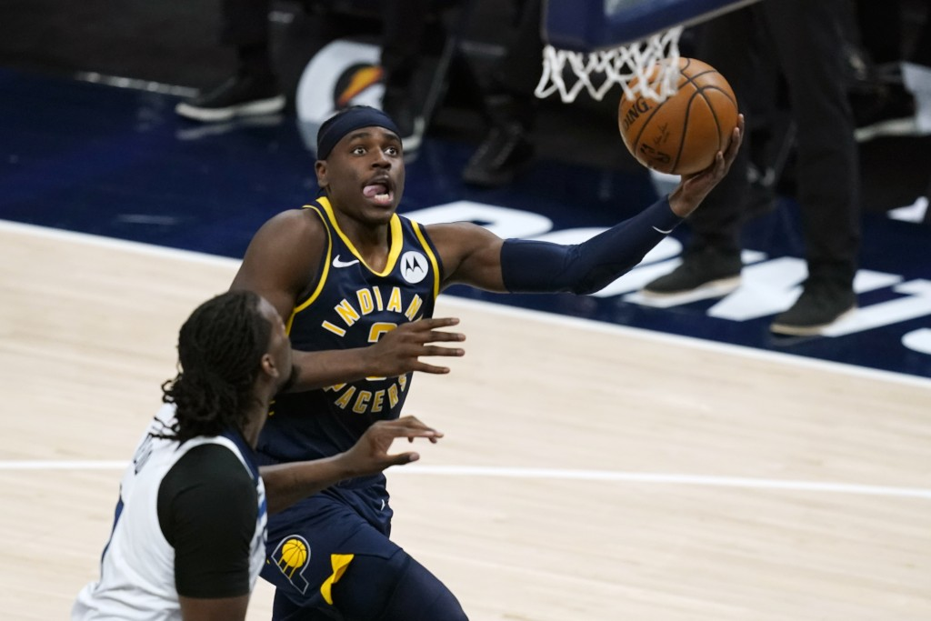 Indiana Pacers' Aaron Holiday (3) puts up a shot against Minnesota Timberwolves' Naz Reid (11) during the second half of an NBA basketball game, Wedne...