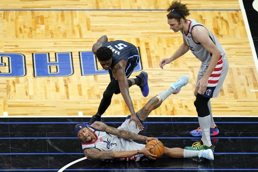 Washington Wizards guard Bradley Beal (3) looks to pass the ball as Orlando Magic center Mo Bamba (5) defends and Wizards center Robin Lopez, right, w...