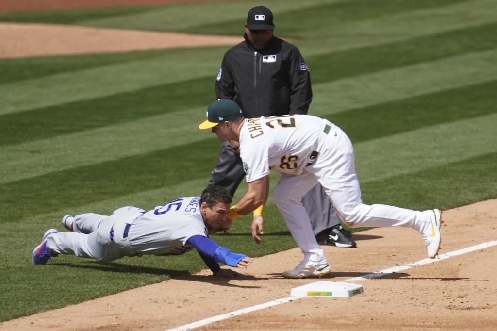 Oakland Athletics third baseman Matt Chapman, right, tags out Los Angeles Dodgers' Austin Barnes at third base during the sixth inning of a baseball g...