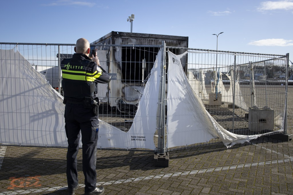 FILE - In this Jan. 24, 2021, file photo, a police officer takes pictures of a burned-out coronavirus testing facility in the fishing village of Urk i...