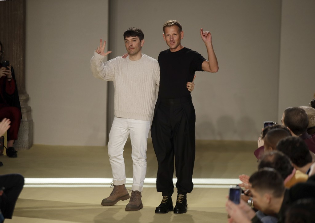 FILE - Creative director Paul Andrew, right, accept applause flanked by menswear designer Guillaume Meilland, at the conclusion of the the Salvatore F...