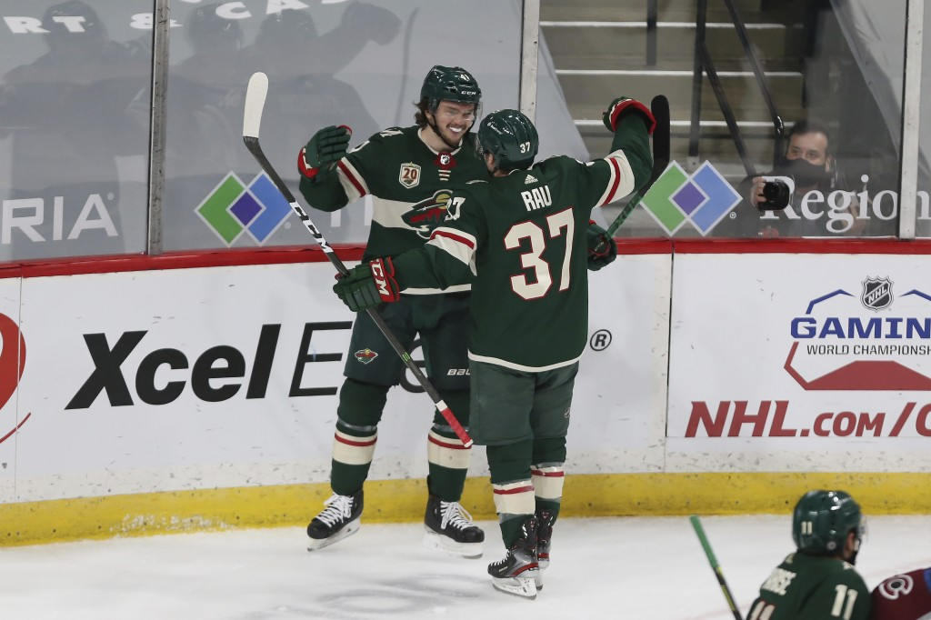 Minnesota Wild's Kyle Rau (37) celebrates with Luke Johnson (41) after Johnson scored a goal against the Colorado Avalanche during the first period of...
