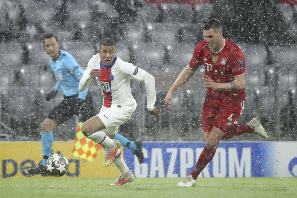 PSG's Kylian Mbappe, left, controls the ball as Bayern's Niklas Suele runs to stop him during the Champions League quarterfinal soccer match between B...