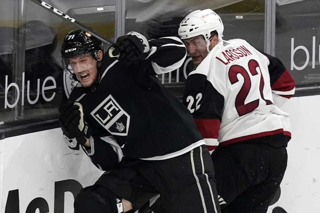 Los Angeles Kings defenseman Austin Strand, left, collides with Arizona Coyotes left wing Johan Larsson during the second period of an NHL hockey game...