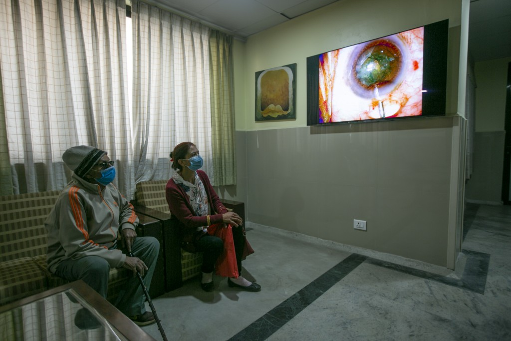 An elderly Nepalese patient, left watches a live feed as Dr. Sanduk Ruit performs cataract surgery at the Tilganga Eye Center in Kathmandu, Nepal, Mar...