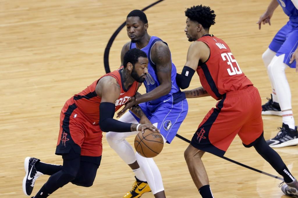 Houston Rockets guard John Wall, left, drives around Dallas Mavericks forward Dorian Finney-Smith (10) as Rockets center Christian Wood (35) sets a sc...