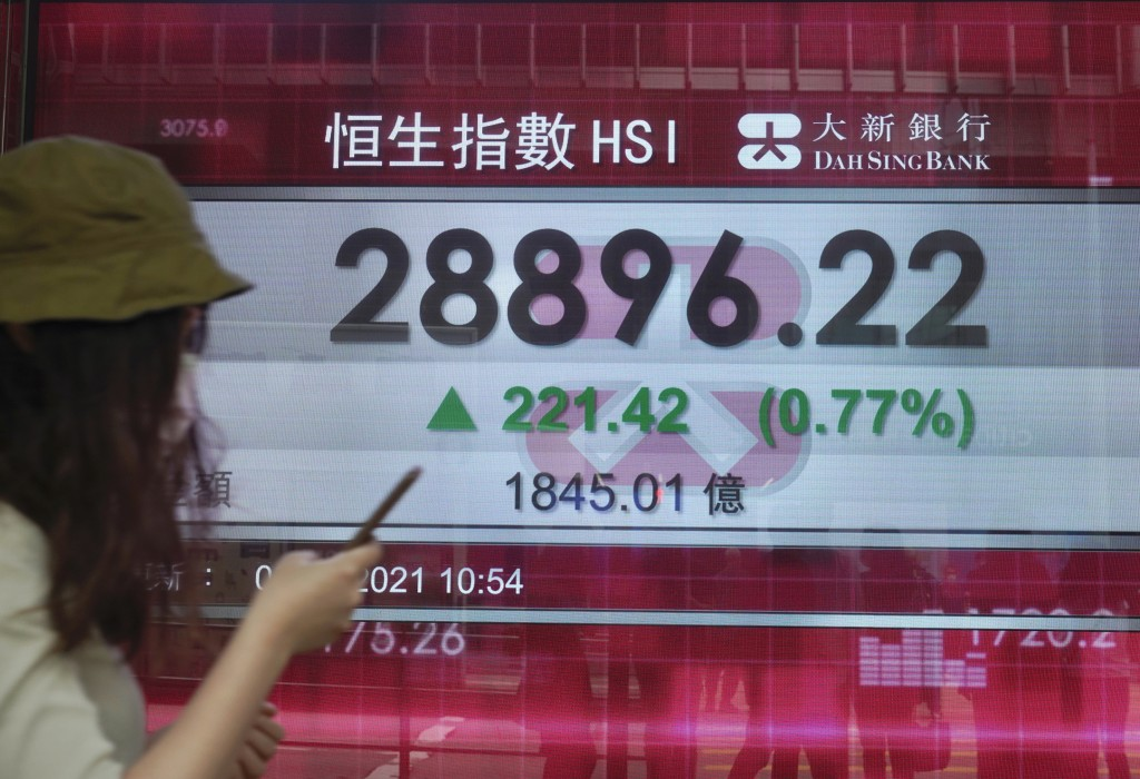 A woman walks past a bank's electronic board showing the Hong Kong share index in Hong Kong Thursday, April 8, 2021. Shares were mostly higher in Asia...