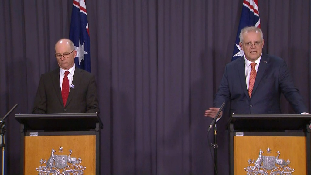 In this image made from video, Australian Prime Minister Scott Morrison, right, with Australian Chief Medical Officer Paul Kelly, speaks during a news...